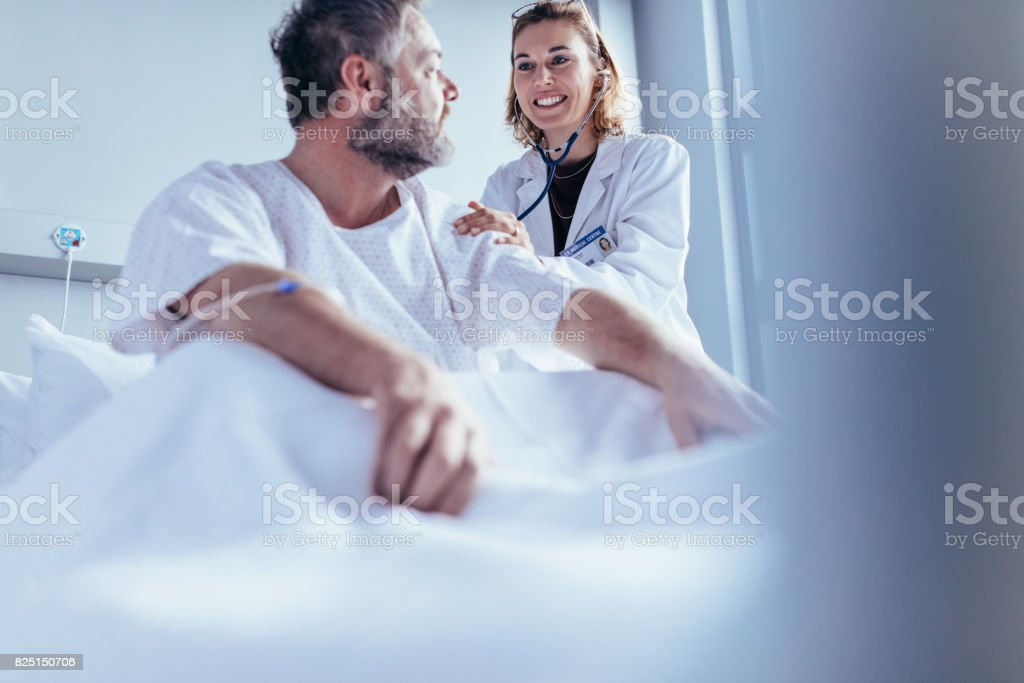 Physician doing routine check up of hospitalised patient stock photo