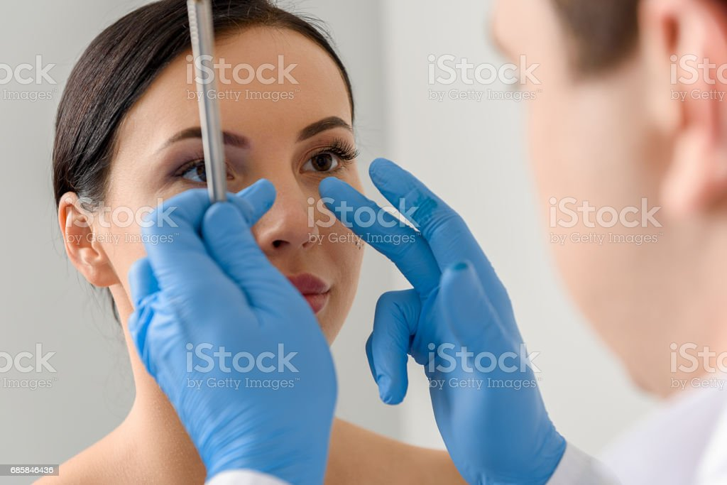 Physician examining face of serene female Focus on doctor hands showing where correct nose of calm woman. She watching at therapeutic Adult Stock Photo