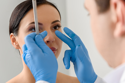 Physician Examining Face Of Serene Female Stock Photo - Download Image Now