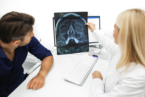 Physician showing a man patient an X-ray of her head and maxillary sinuses during a consultation. Diagnostics and treatment of sinusitis and frontal sinusitis