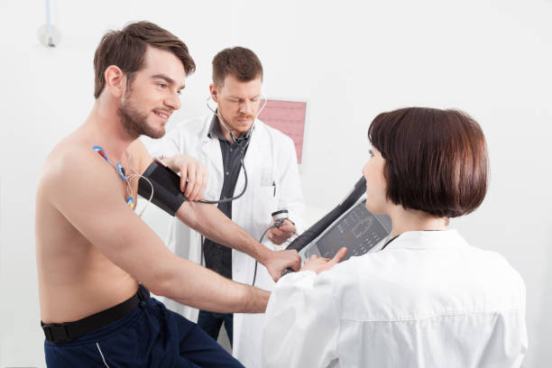 Physician taking a male patients blood pressure stock photo