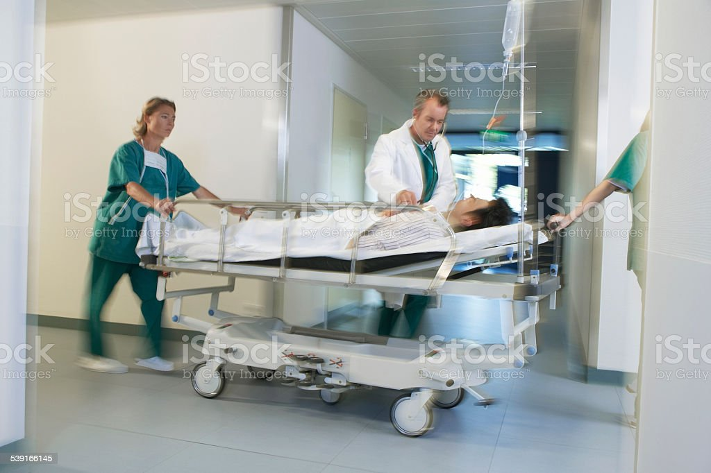 Physicians Moving Patient On Gurney Through Hospital Corridor stock photo