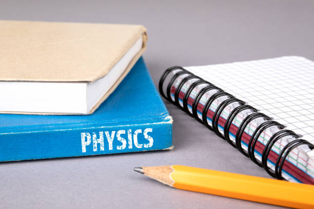 physics concept. blue book on a gray office table - elementary particle stock photos and pictures