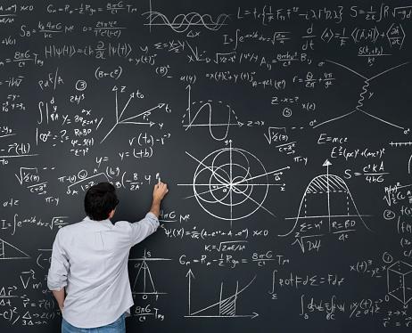 Physics teacher writing math equations on a blackboard