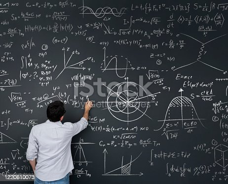 Physics teacher writing math equations on a blackboard – complex mathematics concepts