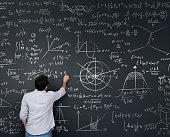 Physics teacher writing math equations on a blackboard – complex mathematics concepts
