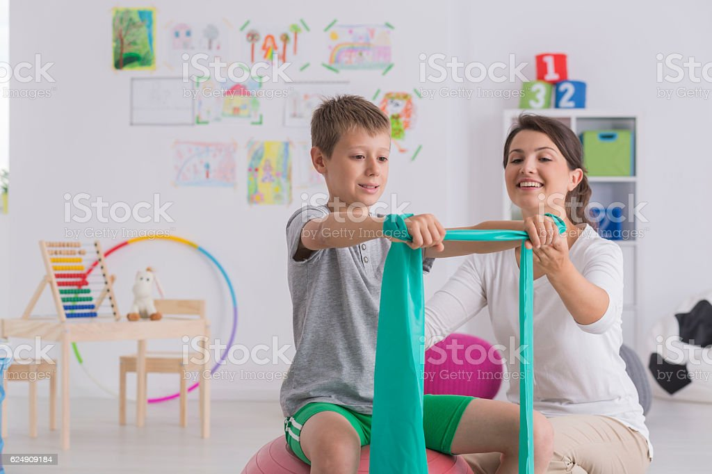 Physiotherapist and boy sitting on a gym ball stock photo