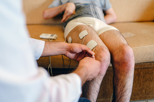 Physiotherapist applying electro stimulation in physical therapy to a young man leg