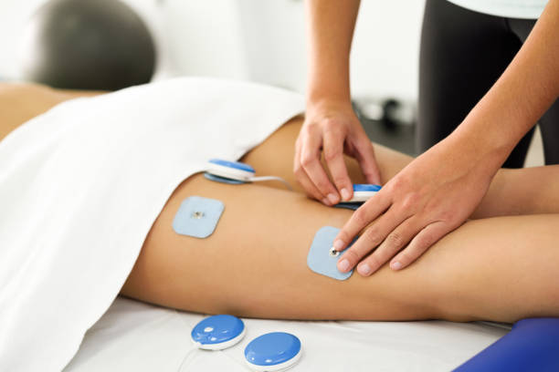 Physiotherapist applying electro stimulation in physical therapy to a young woman leg. stock photo