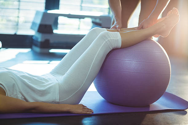 Physiotherapist assisting a patient with exercise ball - foto de stock