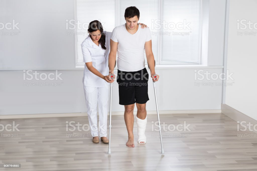 Physiotherapist Assisting Injured Patient To Walk With Crutches stock photo
