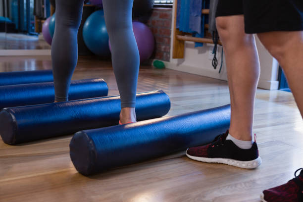 Physiotherapist assisting senior woman in performing exercise on foam roll stock photo