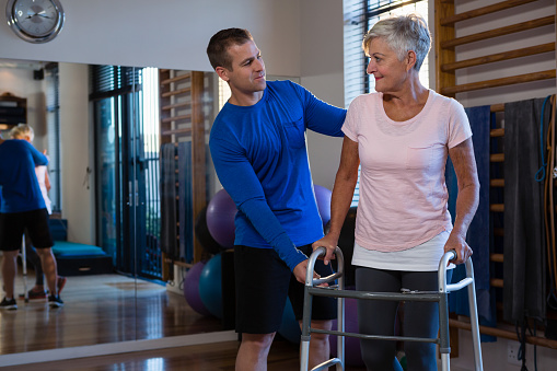 istock Physiotherapist assisting senior woman patient to walk with walking frame 837639212