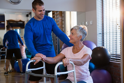 istock Physiotherapist assisting senior woman patient to walk with walking frame 837641420