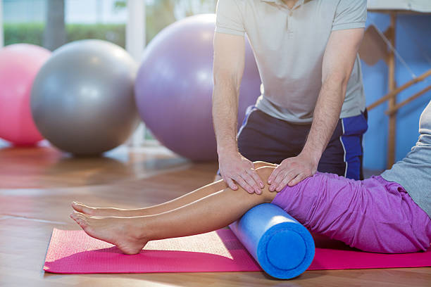 Physiotherapist assisting woman while exercising on exercise mat stock photo