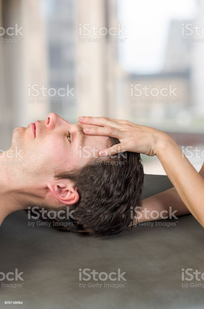 Physiotherapist, chiropractor doing a cranial sacral therapy to a man patient. Activating  trigeminal nerve. Osteopathy. stock photo
