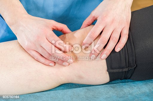 Physiotherapist, chiropractor doing a patellar mobilization, Knee pain. Spraining torn ligaments.