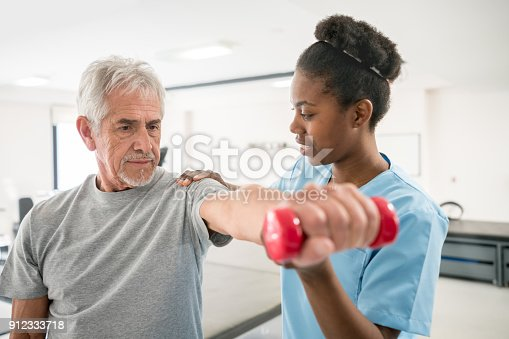 istock Physiotherapist correcting her senior patient with his shoulder posture as he lifts free weights 912333718