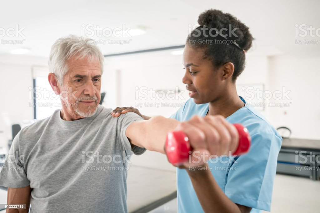Physiotherapist correcting her senior patient with his shoulder posture as he lifts free weights stock photo