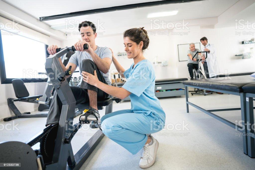 Fisioterapeuta, corrigindo a postura de um paciente em uma bicicleta estática - foto de acervo