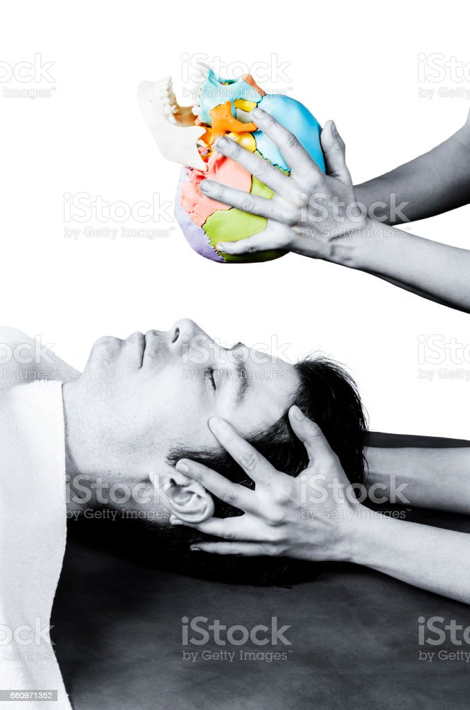 Physiotherapist doing a cranial sacral therapy to a man patient in silhouette studio on white background stock photo