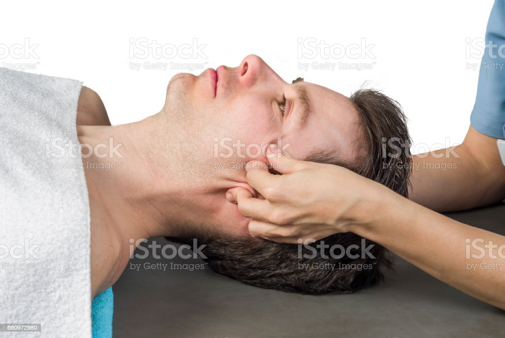 Physiotherapist doing a cranial sacral therapy to a man patient on white background. stock photo