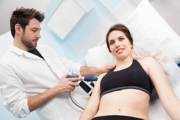 A physiotherapist doing a eswt treatment to a woman stock photo