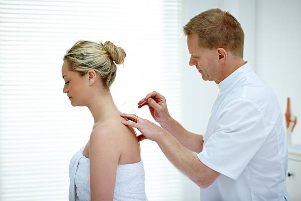 Physiotherapist doing acupuncture on the back of a female patien stock photo