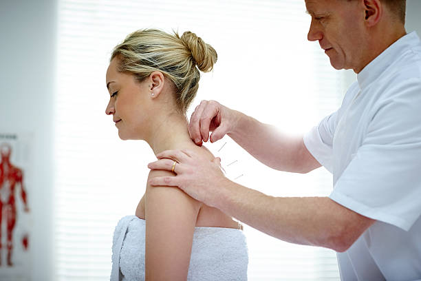 Physiotherapist doing acupuncture on the back of a female patient stock photo