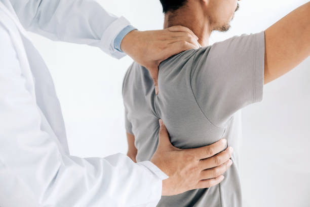 physiotherapist doing healing treatment on man's back.back pain patient, treatment, medical doctor, massage therapist.office syndrome - medicina sportiva foto e immagini stock