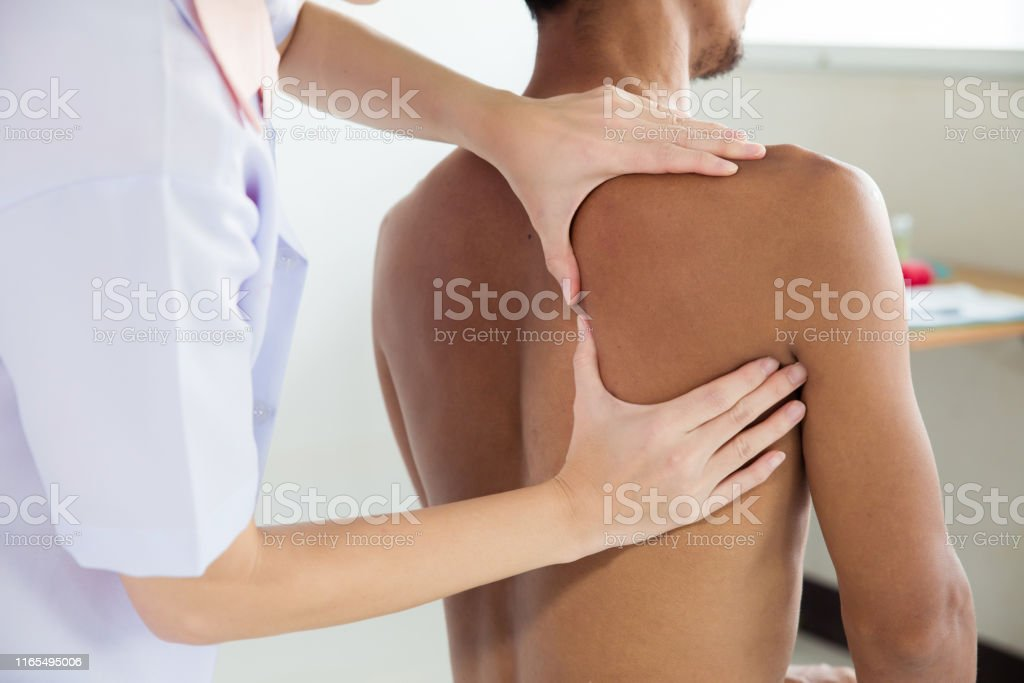 Physiotherapist doing healing treatment on man\'s back.Back pain...