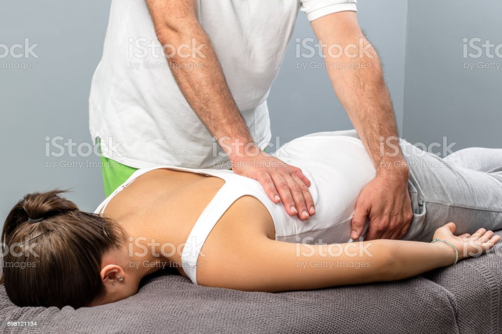 Physiotherapist doing massage on female lower back. stock photo