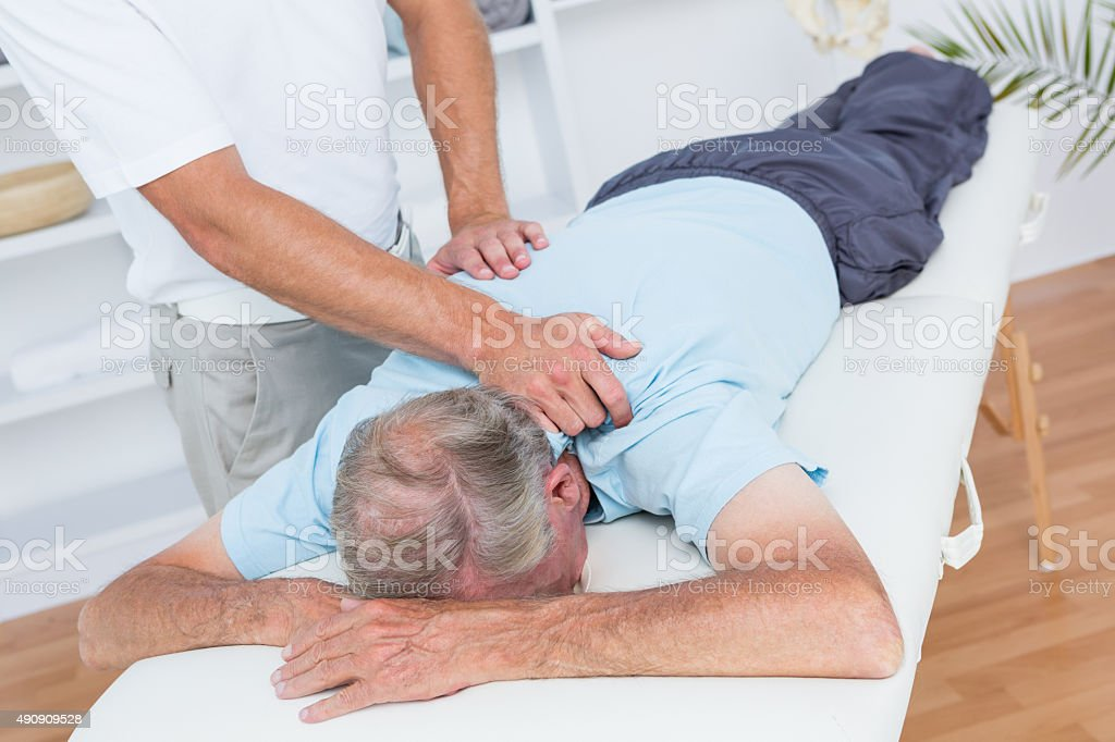 Physiotherapist doing neck massage to his patient stock photo