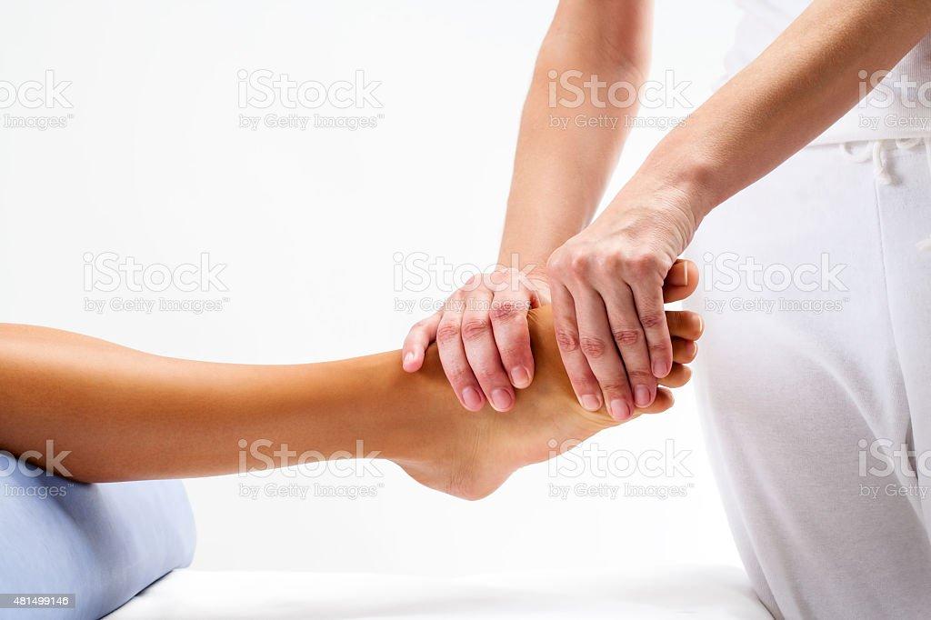 Physiotherapist doing reflexology massage on female foot. stock photo