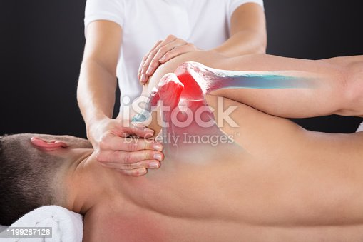 Female Physiotherapist Doing Healing Treatment On Man's Shoulder