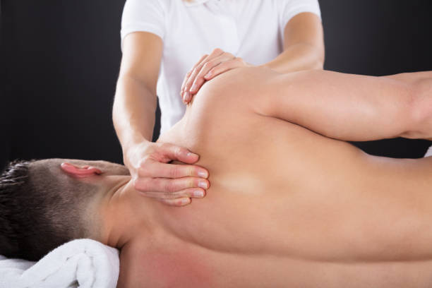 physiotherapist doing treatment on man's shoulder - chiropractic care stock photos and pictures