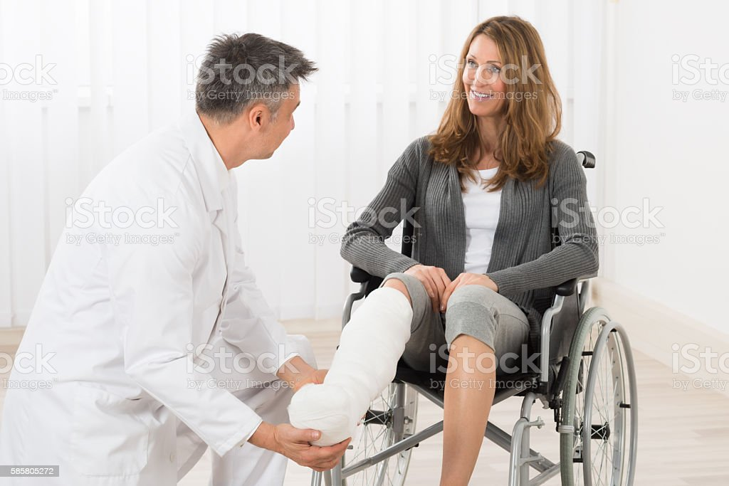 Physiotherapist Examining Leg Of Patient stock photo