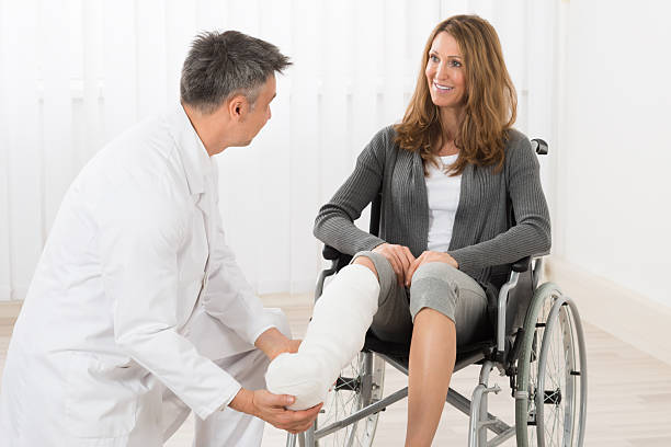 physiotherapist examining leg of patient - broken leg stock photos and pictures