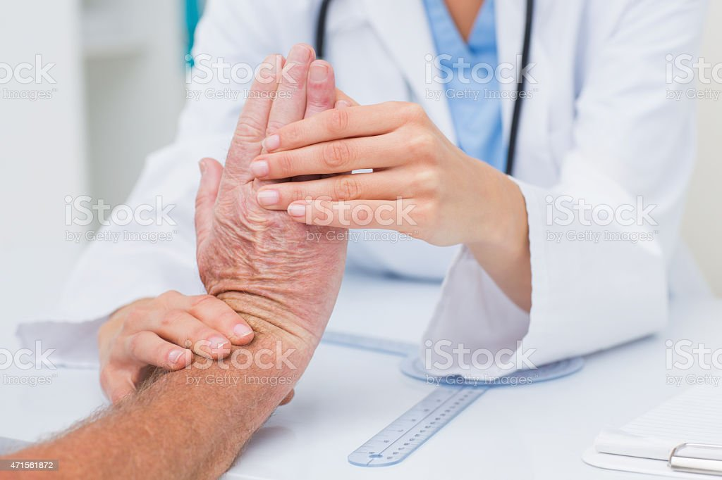 Physiotherapist examining male patients wrist stock photo