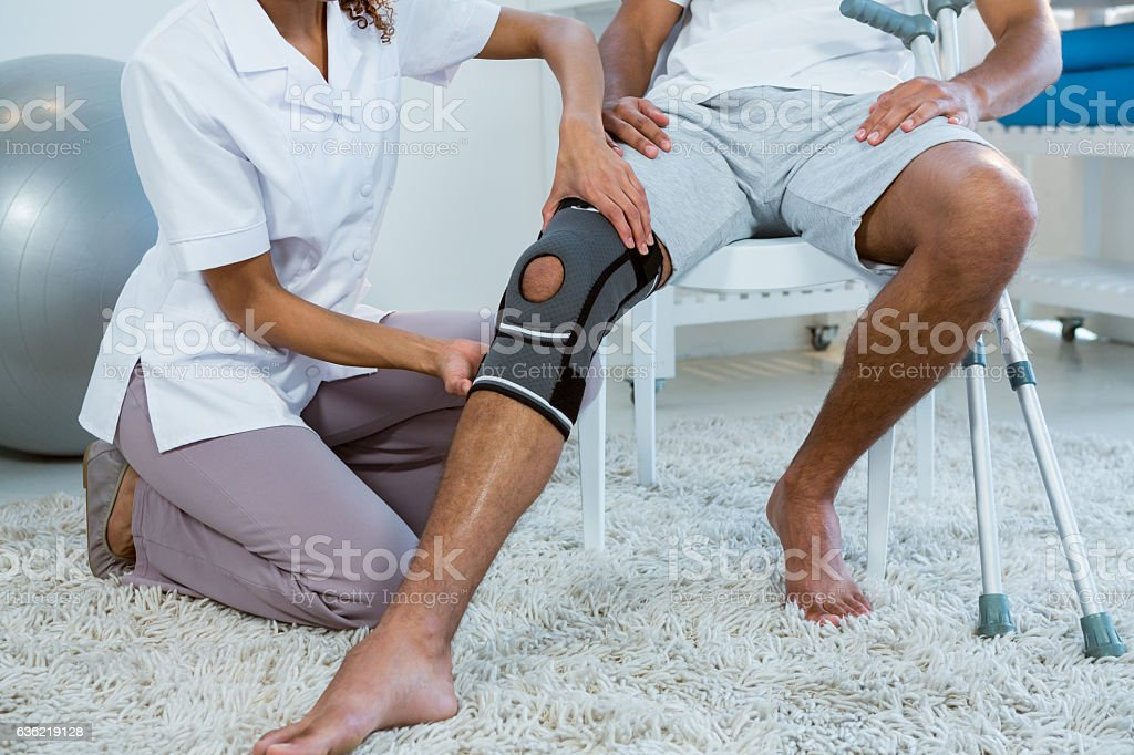 Physiotherapist examining patients knee stock photo