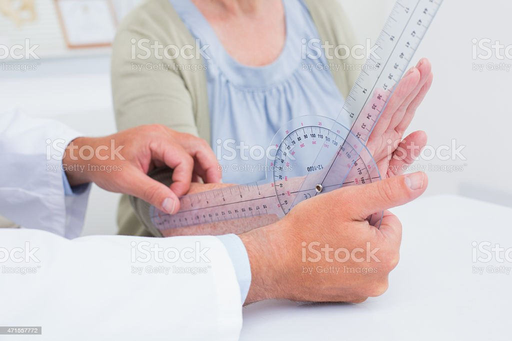 Physiotherapist examining patients wrist with goniometer stock photo