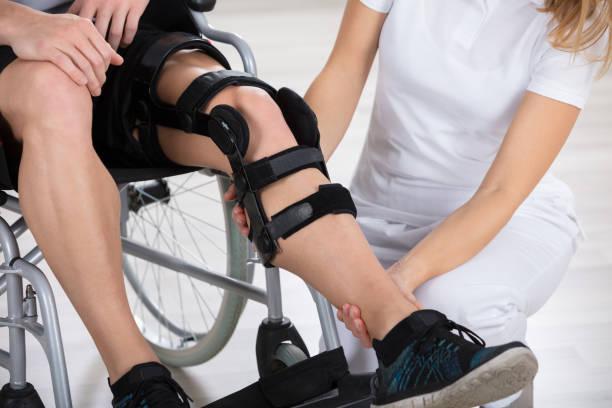 physiotherapist fixing knee braces on man's leg - spina dorsale umana foto e immagini stock