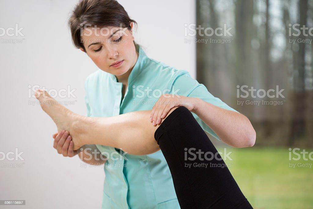 Physiotherapist flexing knee stock photo
