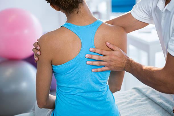 physiotherapist giving back massage to female patient - masaje deportivo fotografías e imágenes de stock