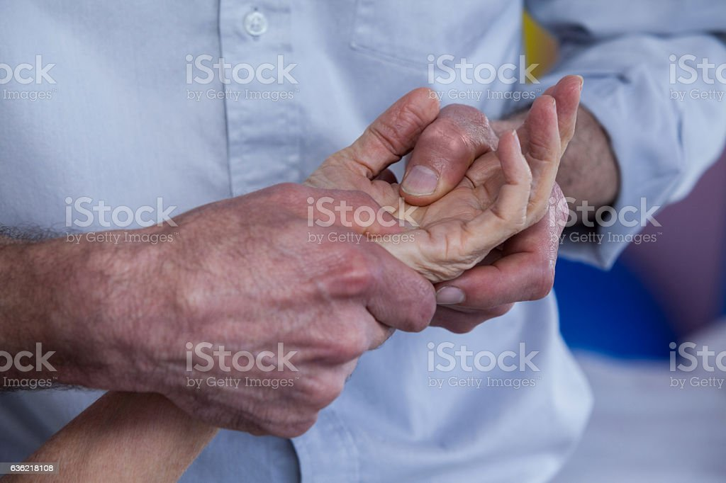 Physiotherapist giving hand massage to a patient stock photo