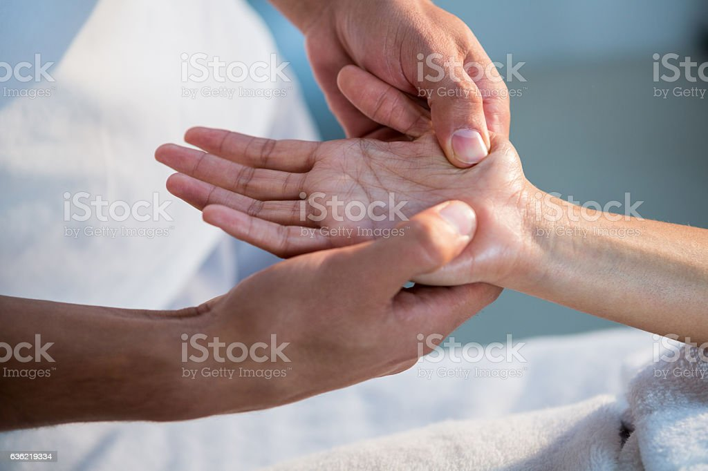 Physiotherapist giving hand massage to a woman stock photo
