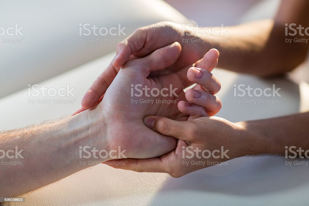 Physiotherapist giving hand massage to patient stock photo
