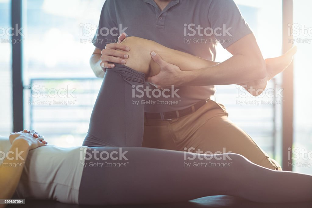Physiotherapist giving knee therapy to a woman stock photo