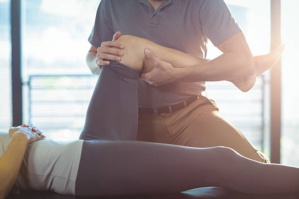 Physiotherapist giving knee therapy to a woman - foto de stock