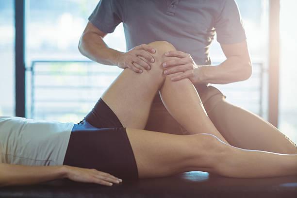 physiotherapist giving knee therapy to a woman - masaje deportivo fotografías e imágenes de stock